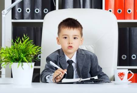 little boy as a businessman, in office Stock Photo - 23525492