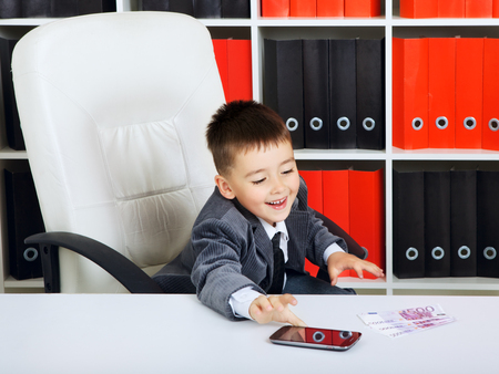 little boy as a businessman, in office photo