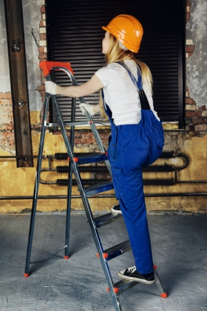 beautiful builder woman in yellow protective helmet on ladder