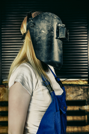 blond woman in overall and welder helmet photo