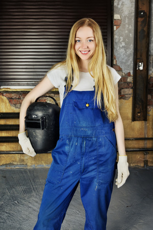beautiful smiling blond woman holding welder helmet photo