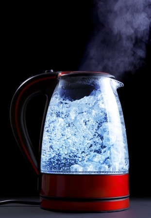 kettle: glass electric kettle with boiling water, black background Stock Photo