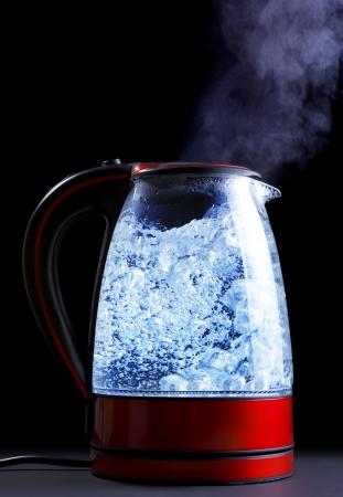 glazen waterkoker met kokend water, zwarte achtergrond Stockfoto