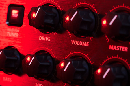 amplifier control panel with knobs, close up photo
