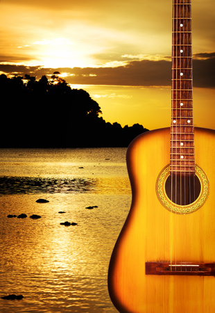 yellow classic acoustic guitar, on nature background photo