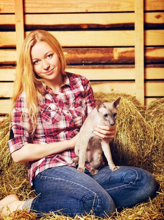 hayloft: hermosa chica con el gato en el pajar en d�a de verano