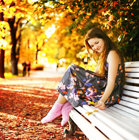 beautiful girl sitting on a bench in autumn park photo