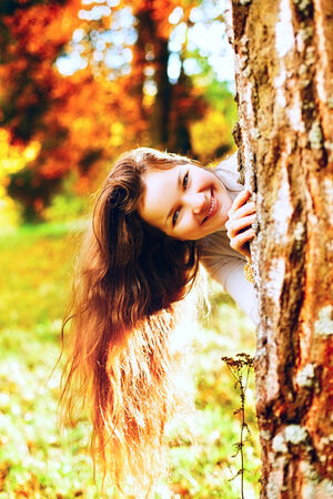 beautiful girl playing and hide for tree in autumn park photo