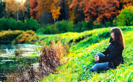 beautiful girl sitting on a shore in autumn forest photo