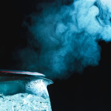tea kettle with boiling water, dark background photo