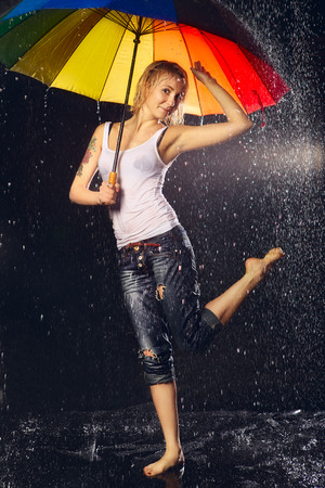 beautiful girl with umbrella under rain, black background photo