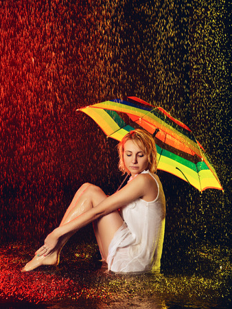 beautiful girl with umbrella under rain, black background photo
