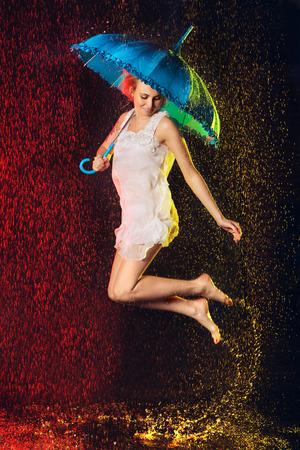 happy jumping girl with umbrella under rain photo