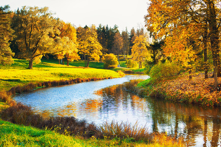 october: autumn landscape in park with river and blue sky