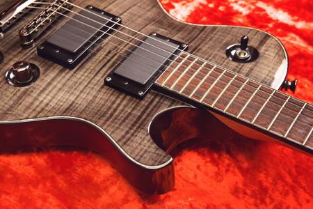 black electric guitar on red velvet background Stock Photo