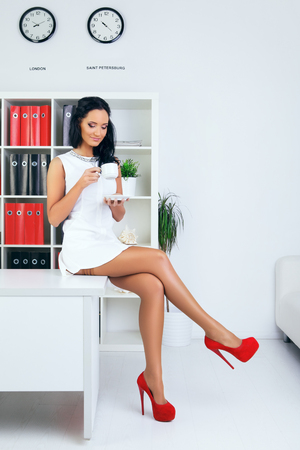 sexy provocative businesswoman drink coffee at office photo