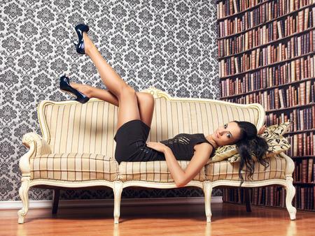 joven mujer provocativa acostado en el sofá, interior