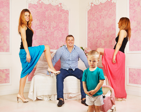 polygamy: happy man with two women and resentful child