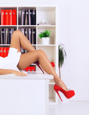 tacones rojos: patas de sexy empresaria extiende sobre la mesa en la oficina Foto de archivo