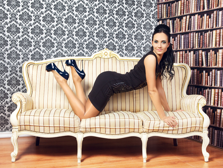 young provocative woman on couch at home Stock Photo