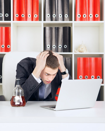 shocked young businessman looking on laptop in his office photo