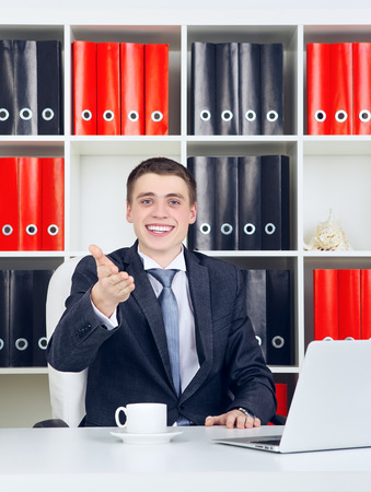 happy young businessman with laptop in his office photo