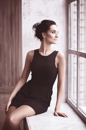 beautiful young woman sitting on windowsill, soft focus, toned photo