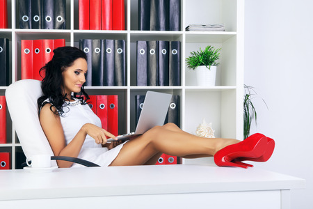 provocative woman: young beautiful businesswoman at office with laptop