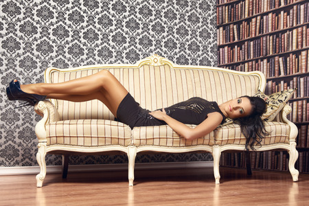 legs heels: young provocative woman on couch at home Stock Photo