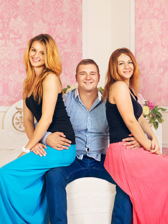 happy man embrace two girls on his knees photo