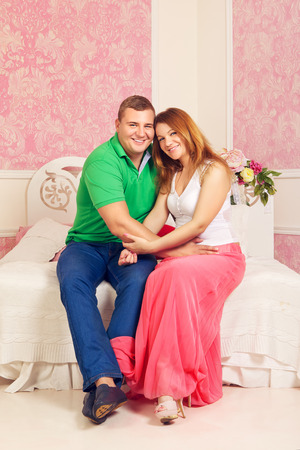 loving mature couple sitting on sofa in pink bedroom photo