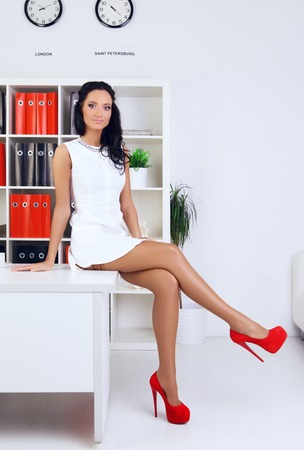 provocative: sexy provocative businesswoman at office sitting on table