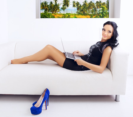 lying on couch: beautiful businesswoman at office on sofa with laptop Stock Photo