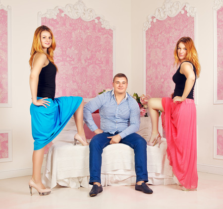 polygamy: happy man and two women in bedroom Stock Photo
