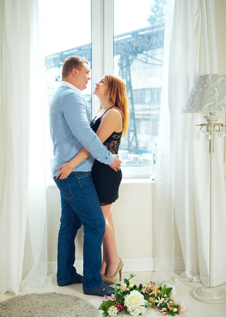 loving mature couple in front of window embrace photo