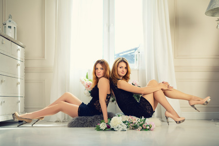 two young sexy girls sitting on a floor in front of window photo