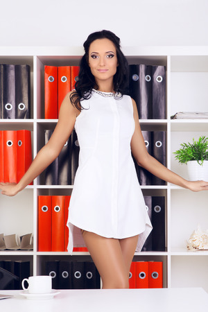 provocative: sexy provocative businesswoman in white dress at office Stock Photo