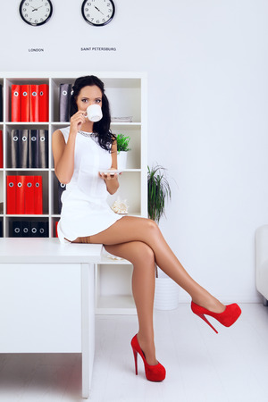 provocative: sexy provocative businesswoman drink coffee at office Stock Photo