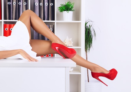 heel: legs of sexy businesswoman lying on table at office