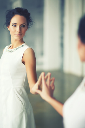 doppelganger: young elegant lady in front of mirror, soft focus