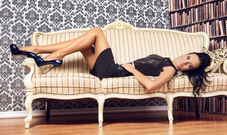 provocative woman: young provocative woman lying on couch, interior Stock Photo