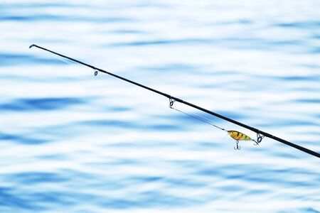 trolling: fishing rod and tackle on blue water background