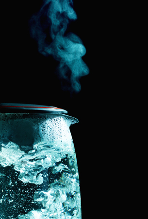 glass electric kettle with boiling water, black background Stock Photo