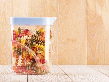 colour in: raw spiral pasta of different color in plastic container Foto de archivo