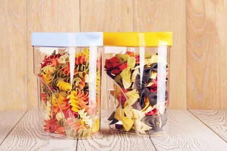envases plasticos: raw fancy pasta of different color in plastic containers