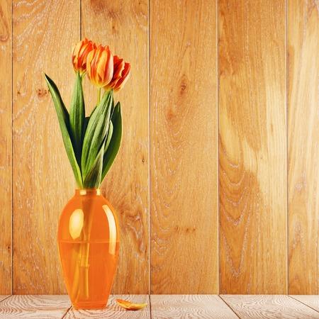 tulip flowers bouquet in vase on wooden background