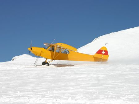 A plane equipped with ski taking off from a glacier (Switzerland)