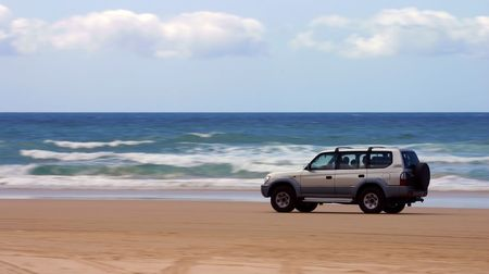 rapidity: Four-wheel-drive SUV moving on a beach (Fraser Island, Australia) Stock Photo