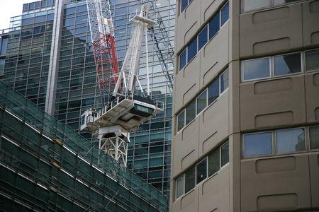 Crane on top of building in dense urban environment Stock Photo