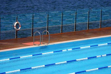 natation: Piscina frente al mar con una boya de la vida y escalera